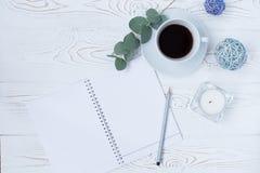 早晨早餐、空的笔记本、铅笔和花的咖啡杯在白色台式 妇女运转的书桌 免版税库存图片