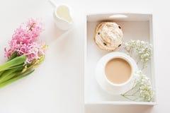 早晨早餐在有一个杯子的春天无奶咖啡用牛奶和酥皮点心在淡色,新鲜的桃红色hyacin花束  库存照片