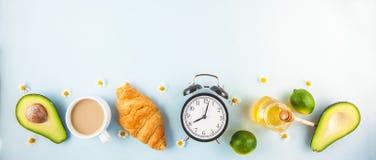 早晨早餐,在唤醒与闹钟的白色杯子新月形面包鲕梨石灰的咖啡快乐,健康早餐新鲜的Co 免版税图库摄影