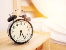 早晨时间背景,在床附近的减速火箭的闹钟在家 免版税库存照片