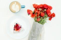 早晨杯子热奶咖啡、鲜美果子莓果蛋糕和鸦片开花在白色桌上的花束 库存照片
