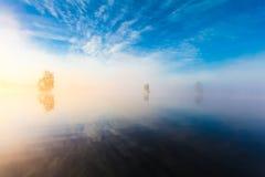 早晨自然风景在湖的有蓝天、云彩、雾薄雾和偏僻的小海岛的 库存图片