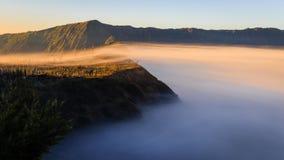 早晨薄雾在布罗莫火山,印度尼西亚包括峭壁村庄 免版税库存照片