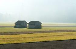 早晨薄雾在有后边领域的一山谷和老木谷仓和森林 免版税库存照片