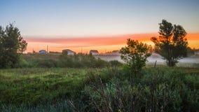 早晨薄雾在黎明,在村庄附近的日出前 库存图片