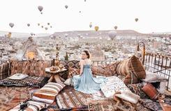 早晨视图在卡帕多细亚 在Goreme妇女的大阳台视图有热空气气球和地毯的 库存图片