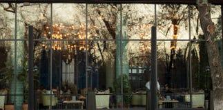 早期的冬时,在玻璃后的餐馆 库存图片