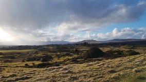 早期的春天小山和山与云彩和阳光 库存照片