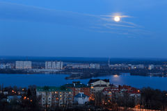 早期的月亮看法在蓝色晚上天空的与反射在河 都市风景 库存照片