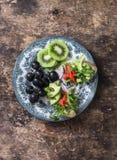 早餐、开胃菜或者快餐板材-三文鱼,鲕梨,芝麻菜bruschetta,葡萄,猕猴桃 健康概念的食物 在木backgroun 免版税库存图片