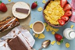早餐、玉米片用新鲜的草莓和牛奶,巧克力黄油用新鲜的酥皮点心在灰色背景 从abov的看法 库存照片