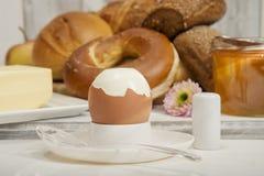早餐、百吉卷、小圆面包和黄油的煮沸的鸡蛋 图库摄影