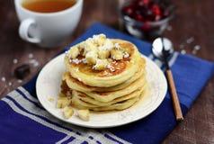 早餐与香蕉和椰子剥落的酸奶干酪薄煎饼 免版税库存图片