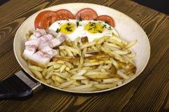 早餐二 煎锅用两个煎蛋和油煎的pota 免版税库存图片
