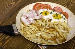 早餐二 煎锅用两个煎蛋和油煎的pota 免版税图库摄影