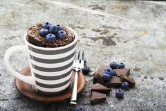 早餐健康快餐 巧克力杯子杯形蛋糕用蓝莓和巧克力片在一个灰色镶边陶瓷杯子 库存图片