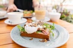 早餐和咖啡在夏天咖啡馆 在一个小圆面包奶油蛋卷的三明治用烟肉、蘑菇、芝麻菜和荷包蛋 库存照片