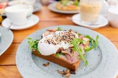 早餐和咖啡在夏天咖啡馆 在一个小圆面包奶油蛋卷的三明治用烟肉、蘑菇、芝麻菜和荷包蛋 免版税库存照片