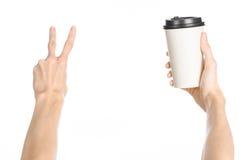 早餐和咖啡题材:拿着有一个棕色塑料盖帽的人的手白色空的纸咖啡杯隔绝在一白色backgroun 库存图片