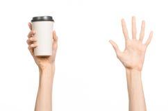 早餐和咖啡题材:拿着有一个棕色塑料盖帽的人的手白色空的纸咖啡杯隔绝在一白色backgroun 免版税库存图片