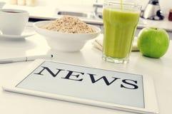 早餐和新闻在厨房用桌上 免版税库存图片