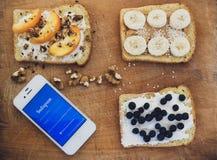 早餐和电话的多士有在木背景的Instagram的 免版税库存照片