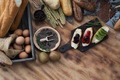 早餐和被烘烤的面包概念 新鲜的芬芳面包和鸡蛋在木桌上 新鲜面包和咖啡和麦子在木黑色 库存图片