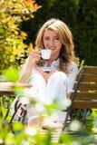 早餐咖啡饮用的庭院妇女 免版税库存图片