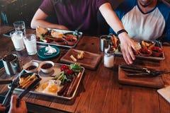 早餐咖啡馆蛋糕咖啡杯 朋友吃在咖啡馆的早餐 年轻人将开始他们的食物和饮料 库存照片