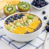 早餐圆滑的人碗用matcha绿茶,猕猴桃、香蕉和杏仁挤奶,冠上用莓果、果子、坚果和种子,正方形 库存照片