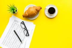 早餐在办公室用新月形面包和咖啡在工作书桌上有文件的和玻璃在黄色背景顶视图 免版税库存照片