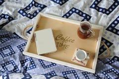 早餐在河床上 书、水罐和一杯咖啡在手工制造一个木的盘子的 蓝色亚麻布 库存照片