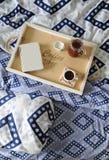 早餐在河床上 书、水罐和一杯咖啡在手工制造一个木的盘子的 蓝色亚麻布 图库摄影