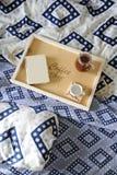 早餐在河床上 书、水罐和一杯咖啡在手工制造一个木的盘子的 蓝色亚麻布 免版税图库摄影