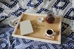 早餐在河床上 书、水罐和一杯咖啡在手工制造一个木的盘子的 蓝色亚麻布 免版税库存图片