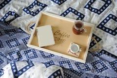 早餐在河床上 书、水罐和一杯咖啡在手工制造一个木的盘子的 蓝色亚麻布 免版税库存照片