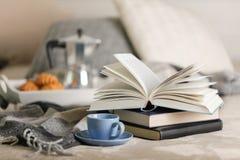 早餐在河床上 在一个白色盘子上有咖啡壶、咖啡蓝色杯子和新月形面包 图库摄影