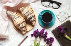 早餐在河床上 早晨、新月形面包、咖啡、花和一个笔记本有笔的 计划 免版税库存照片