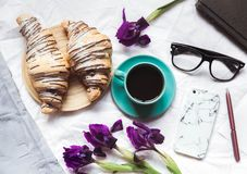 早餐在河床上 早晨、新月形面包、咖啡、花和一个笔记本有笔的 计划 图库摄影
