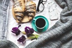 早餐在河床上 早晨、新月形面包、咖啡、花和一个笔记本有笔的 计划 库存图片
