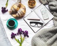 早餐在河床上 早晨、新月形面包、咖啡、花和一个笔记本有笔的 计划 免版税图库摄影