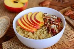 早餐奎奴亚藜粥用苹果和胡说的顶部 素食奎奴亚藜粥用苹果和山核桃果在一个白色碗 免版税图库摄影