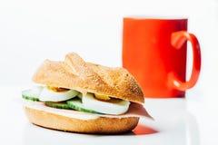 早餐小圆面包三明治和红色咖啡杯 免版税库存照片