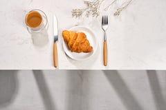 早餐平的位置用新月形面包和无奶咖啡 免版税库存照片