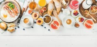 早餐快餐和饮料在白色木背景设置了 免版税库存照片