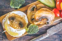 早餐怂恿本尼迪克特荷包蛋用泛油煎的蘑菇和菜 关闭 选择聚焦 图库摄影