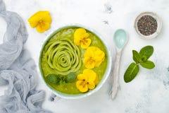 早餐戒毒所绿色圆滑的人碗冠上与猕猴桃玫瑰色和可食的蝴蝶花开花 免版税库存图片