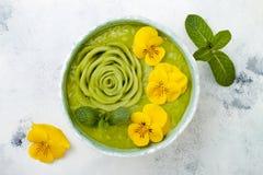 早餐戒毒所绿色圆滑的人碗冠上与猕猴桃玫瑰色和可食的蝴蝶花开花 库存图片