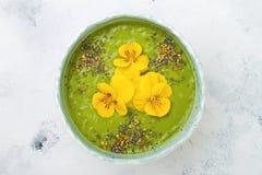 早餐戒毒所绿色圆滑的人碗冠上了与superfoods、chia种子、蜂花粉和可食的花 顶上,平的位置 免版税库存图片