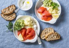 早餐或快餐两块板材-怂恿在蓝色背景的沙拉、三文鱼和鲕梨纯汁浓汤,顶视图 健康的食物 库存照片